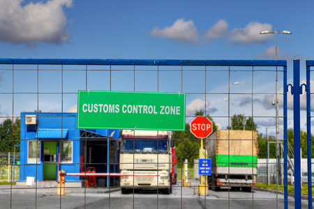 Vrachtwagens passeren de douanecontrolepost van het logistieke complex.