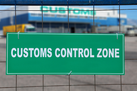White inscription on a green background, customs control zone, in front of a logistics terminal with warehouse storage and customs clearance services.