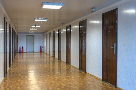 Long couloir de bureau avec de nombreuses portes en bois rouge foncé.