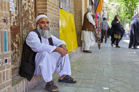 Yazd, Iran - April 22, 2017: An elderly bearded man in white Muslim clothes, fingering rosary, sitting on the threshold of a brick house, on a busy street.