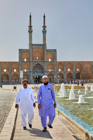Yazd, Iran - April 22, 2017: Two Islamic clerics stroll through the square with a fountain in a sunny day on the background of Amir Chakhmaq mosque.