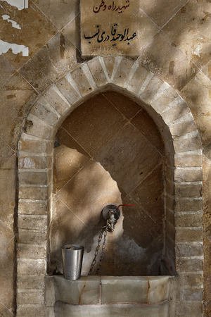 Stone arch with public drinking fountain in Yazd, Iran.
