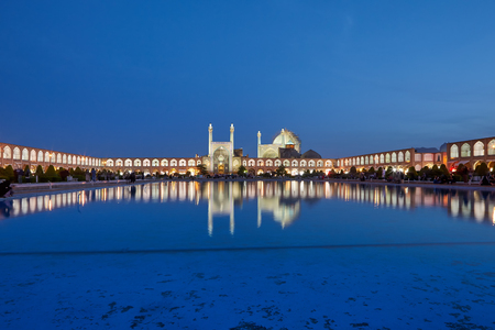 Isfahan, Iran - April 23, 2017: Evening view of Naghsh-e Jahan Square with Shah mosque and  shopping arcades at night illumination, which are reflected in  water of decorative fountain pond. Zdjęcie Seryjne