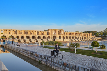 Isfahan, Iran - April 24, 2017: A man drives a bicycle alongside him along the embankment of the Zayandeh River against the backdrop of Khaju Bridge or Pol-e Khaju on a sunny morning.