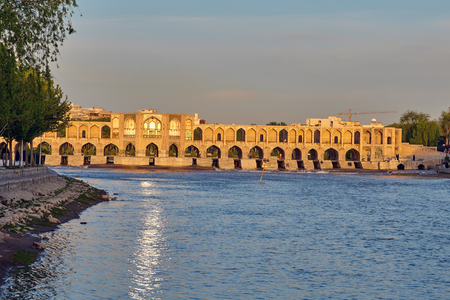 Isfahan, Iran - April 24, 2017: The river Zayandeh with the Khaju bridge and sunlight on the surface of the water, early morning. Editorial