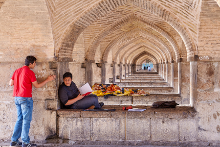Isfahan, Iran - April 24, 2017: Young man reading a record in a notebook while lying on a rock in a vaulted arched passage under the Khaju bridge.