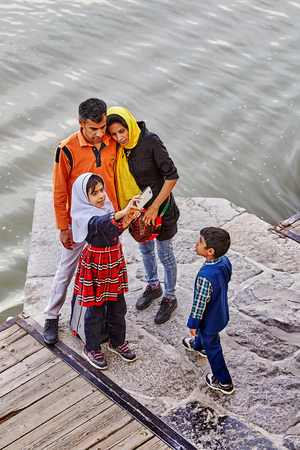 Isfahan, Iran - April 24, 2017: An Iranian family of four takes pictures of themselves on the Khaju bridge.