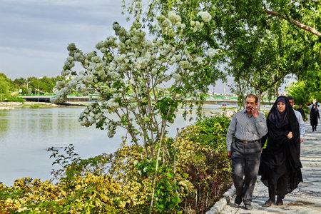 Isfahan, Iran - April 24, 2017: A mature Iranian couple walks along the embankment of the city river.