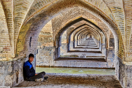 Isfahan, Iran - April 24, 2017: The arched line under the bridge Allahverdi Khan above the river Zayandeh, one young man sits on a stone slab, cross-legged.