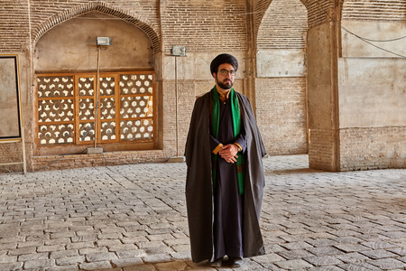 Isfahan, Iran - April 24, 2017: Iranian mullah in traditional clothes stands in the courtyard of the mosque. Редакционное