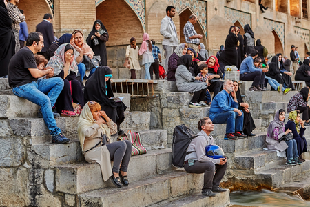 Isfahan, Iran - April 24, 2017: Many people meet sunset sitting on steps of ancient bridge. Editorial