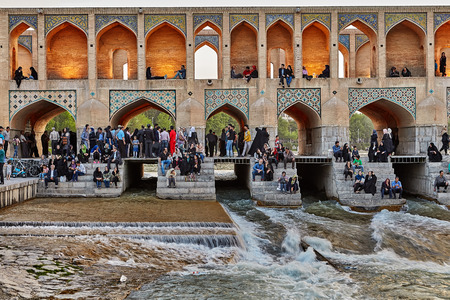 Isfahan, Iran - April 24, 2017: Iranians are sitting on the steps of the Khaju bridge at twilight waiting for the sunset.