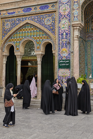 Tehran, Iran - April 27, 2017: Iranian women in hijab stand near Shah Abdol Azim Shrine and take photos. Editorial