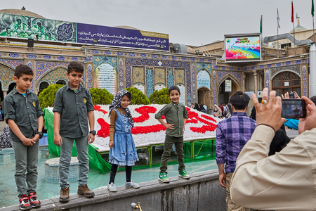 Tehran, Iran - April 27, 2017: man takes pictures of Iranian boys and a girl near The Shah Abdol Azim Shrine. Redactioneel