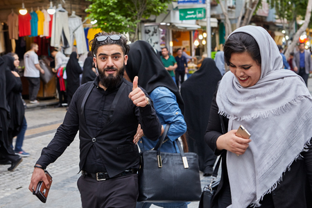 Tehran, Iran - April 27, 2017: Iranian man and woman in hijab are walking along the street of Shahre Rey area.