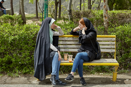 Tehran, Iran - April 28, 2017: two Iranian women in hijabs sit on a bench in a park with drinks and chat with each other.