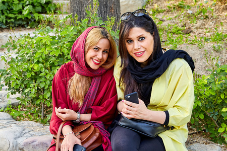 Tehran, Iran - April 28, 2017: two Iranian women in religious veil are sitting in the park and smiling.