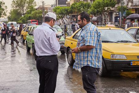 Tehran, Iran - April 29, 2017: Iranian policeman on the street checks drivers drivers license. Redactioneel