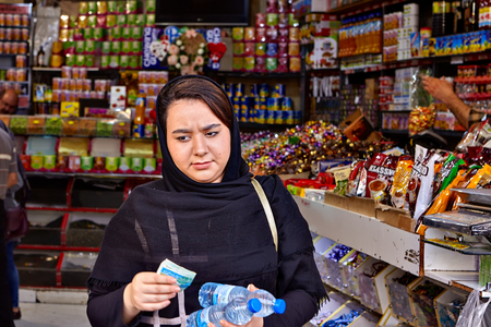 Tehran, Iran - April 29, 2017: A young woman dressed in an Islamic headscarf comes out of a grocery store with two bottles of drinking water in her hands.