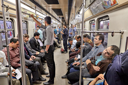 Tehran, Iran - April 29, 2017: Muslims ride in the subway train, Iranian men stand and hold on to the railings.
