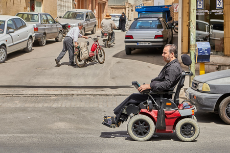 Kashan, Iran - April 27, 2017: Handicapped Man in city center riding a disability bike.