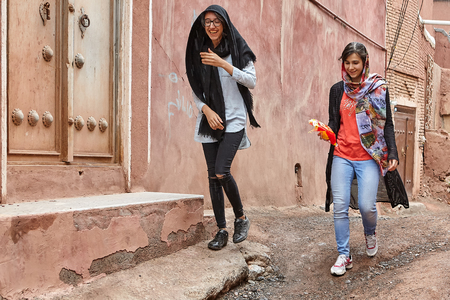 Abyaneh, Iran - April 26, 2017: two young women in hijabs are walking along a narrow street in the traditional village in the mountains and laughing. Editorial