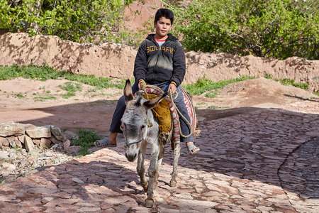 Abyaneh, Iran - April 26, 2017: Iranian boy is riding on a donkey in the  traditional village in the mountains. Redactioneel
