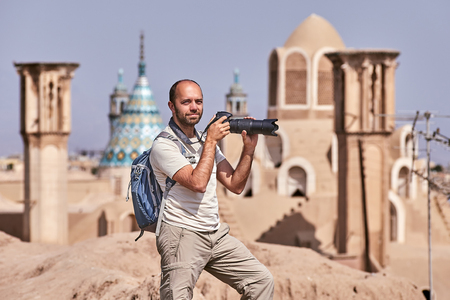 Tourist during single travel takes photo in ancient town. Stock Photo