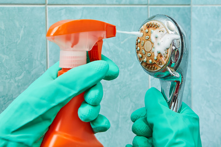 Hands in green rubber protective gloves wash the head of the shower with the help of a cleaning spray.