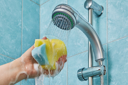 Shower gel foams and flows down through the sponge for bathroom which is compressed in a human hand stretched under flow of water flowing from the shower head.