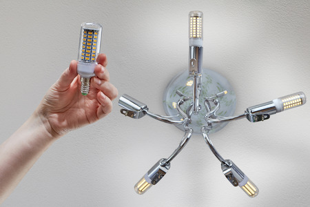 The hand holds a household LED corn lamp before installation in a chrome ceiling chandelier. Stockfoto