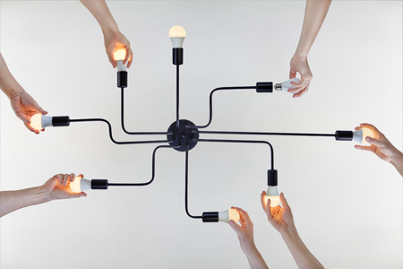 Concept of team spirit, or teamwork on example of team work when replacing LED lamps in a ceiling chandelier. Banque d'images