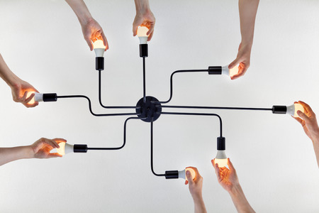 Concept of teamwork, or shared purpose on example of united actions when replacing LED lamps in a ceiling lighting.