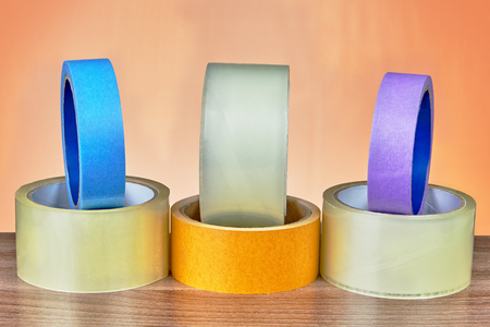 Different types of adhesive tape are lined on an orange background.