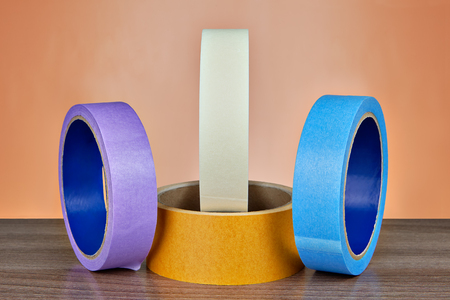 Four reels of multi colored adhesive tape on an orange background.