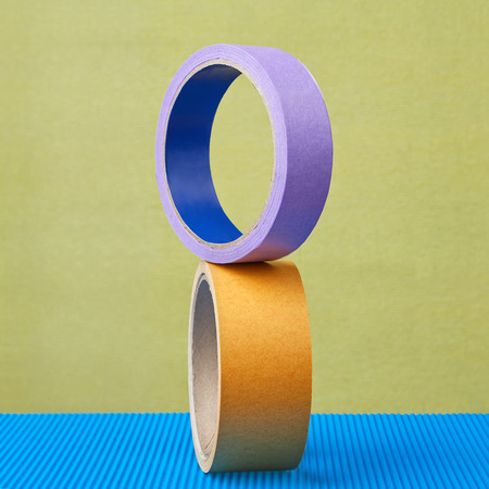 Two rollers of colored adhesive tape are balanced on a lilac background.