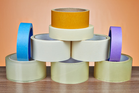 Many rolls of scotch packing tape, and masking tape is stacked in form of pyramid, on orange background. Stock fotó