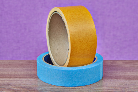 One roll of yellow double-sided tape and one roll masking tape blue lie on a table on a purple background.