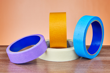Four colored rolls of  paper and plastic  duct tape lie on the table.