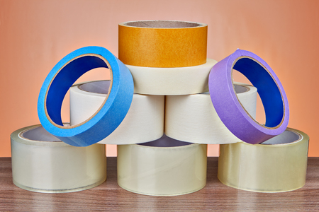 Set of scotch packing tape is stacked in form of pyramid, on orange background.