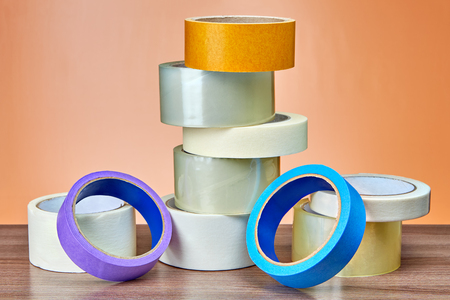 Transparent duct tape for packing and painters masking tape in small heap on table.