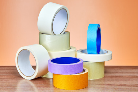 Duct tape in assortment lies on table against background of orange wall. Stock Photo