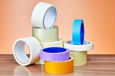 La cinta adhesiva en el surtido se encuentra en la mesa contra el fondo de la pared naranja. Foto de archivo