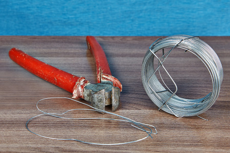 End cutting nipper with red handles and one roll of steel wire. Фото со стока