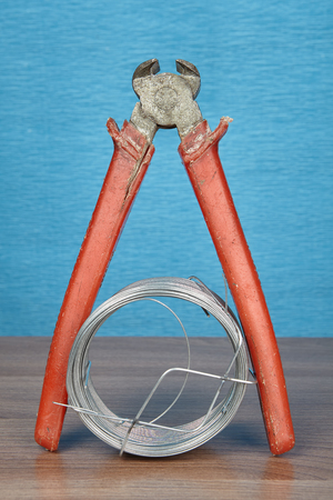 End cutter pliers with red plastic handles and steel wire coil lies on wooden plank, blue backdrop.