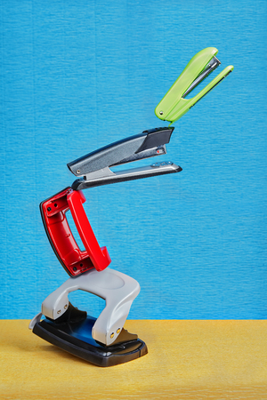 Few colored hole punchers and staplers float in air under non gravity conditions on a blue backdrop.