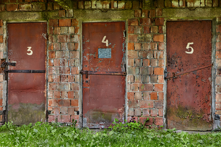 Three worn red doors, upholstered in metal, and numbered three, four, five in an abandoned warehouse in brick building. Reklamní fotografie
