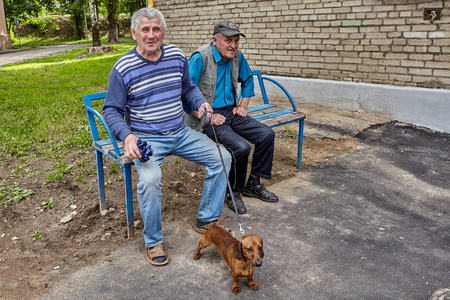 Vitebsk, Belarus - July 7, 2018: two elderly Belarusian men sit on bench in park, one of them holds dachshund on leash.