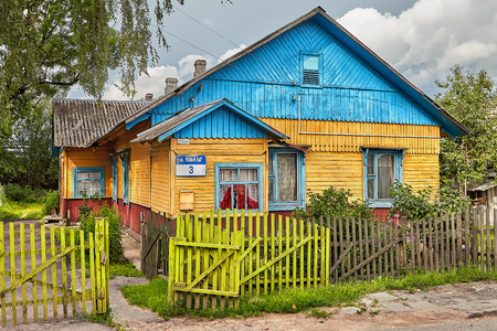 Vitebsk, Belarus - July 7, 2018: old wooden rural house with blue roof, surrounded by fence, stands in Belarusian village.