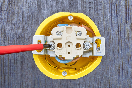 Repair of household electrical wiring, installation of power socket, an electricians hand with hand screwdriver, close-up.